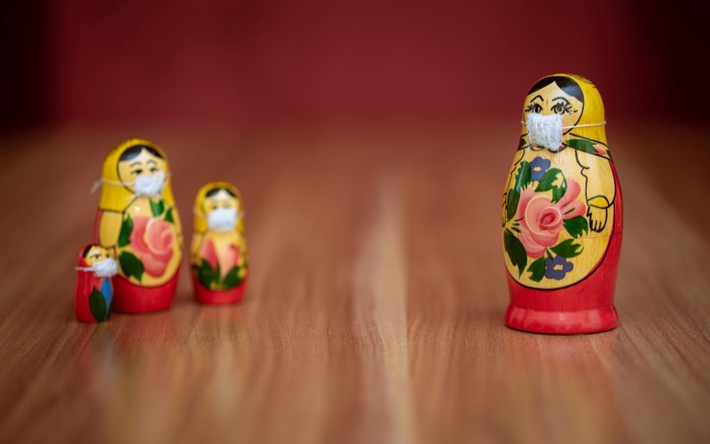 3 babushka dolls wearing face masks standing apart
